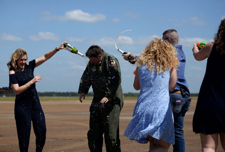 Lt. Col. Brent Green, 43rd FTS assistant director of operations, is sprayed with champagne and water by his family April 13, 2018, on Columbus Air Force Base, Mississippi. He is one of the original cadre in the Firebirds. It was shortly after the squadron expanded in 1999 from teaching only in the T-38C Talon to teaching all airframes that he was hired. Green has spent 22 years of his career in a full-time capacity learning or teaching in the T-37, T-38 and T-6A Texan II on Columbus AFB. (U.S. Air Force photo by Airman 1st Class Keith Holcomb)
