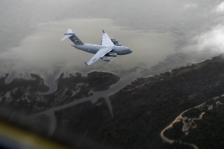 A C-17 Globemaster III aircraft flies over the N.C. coast line on the way to the North Carolina Air National Guard Base, Charlotte Douglas International Airport, April 7, 2018. The airframes homecoming will be marked by an Acceptance Ceremony. The 145th Airlift Wing (AW) was selected to transition from the C-130 Hercules aircraft to the C-17 Globemaster III aircraft 18 months ago, and the airframe will carry the units airlift mission into the future. The first two aircraft of eight to come to the 145th AW were previously assigned to the active duty wings at Joint Base Charleston, S.C. or Joint Base Lewis-McChord, Wash.