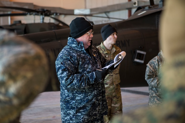 Lt. Cmrd. John Ladd, the rotary officer for IRT Arctic Care 18, provides a safety brief to service members supporting Innovative Readiness Training Arctic Care 2018 prior to boarding a U.S. Army UH-60 Black Hawk helicopter as they prepare for departure from the flight line, Kotzebue, Alaska, April 14, 2018.  IRT Arctic Care 2018 is comprised of a joint and multi-national force providing medical, dental, optometry and veterinary care for underserved villages in the Maniilaq Service Area, April 16-24. (U.S. Marine Corps photo by Lance Cpl. Ricardo Davila