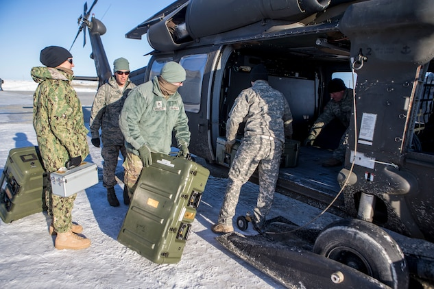 Service members load a U.S. Army UH-60 Black Hawk helicopter with gear and supplies in support of Innovative Readiness Training Arctic Care 2018, as they prepare to depart Kotzebue, Alaska, and travel to outlying villages, April 14, 2018. Service members in support of IRT Arctic Care will conduct critical mission training and logistical movements in order to simulate military/civilian humanitarian operations and health care delivery in time of crisis, conflict or disaster. (U.S. Marine Corps photo by Lance Cpl. Ricardo Davila)
