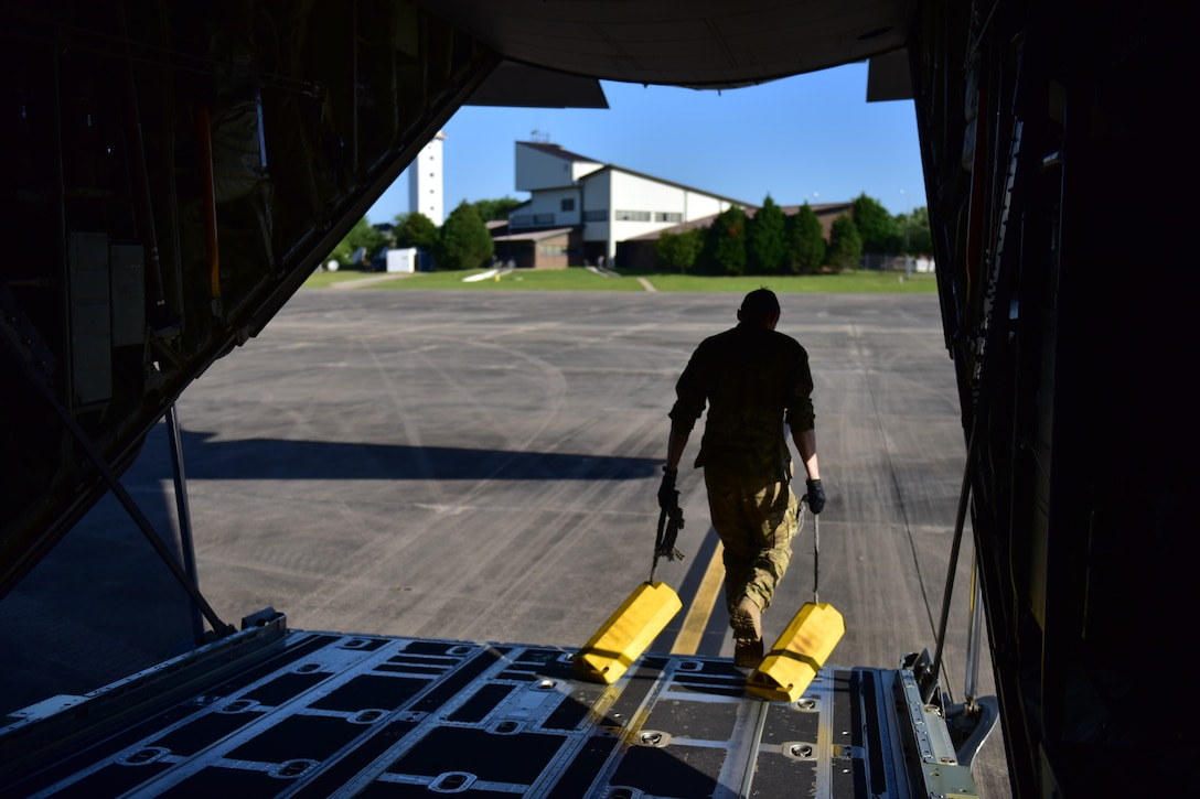 Man walks out of the back of a C-130J a tire block in each hand.