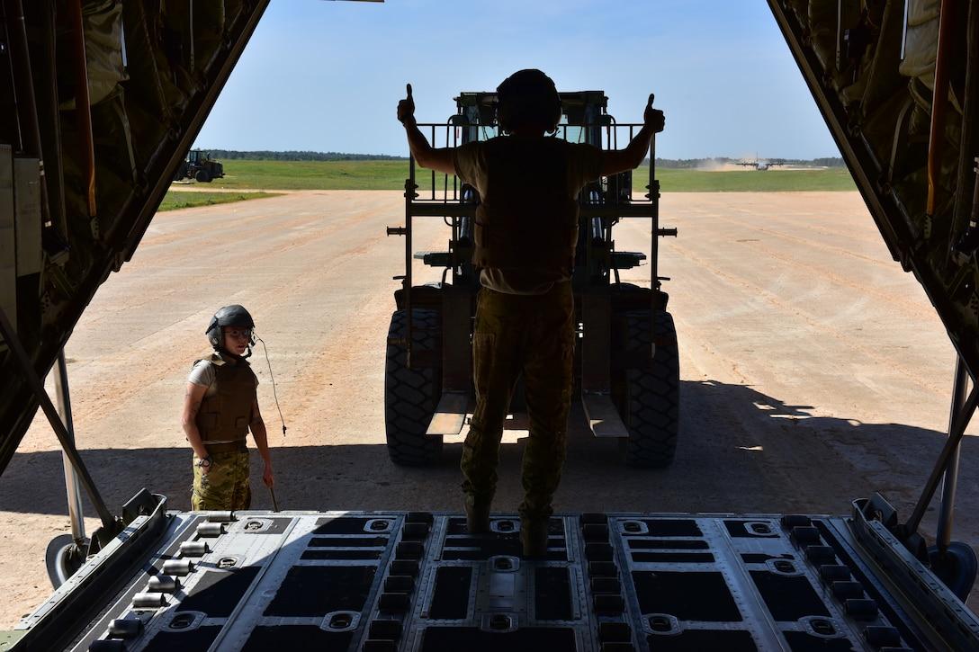 Man directs forklift towards back of C-130J.