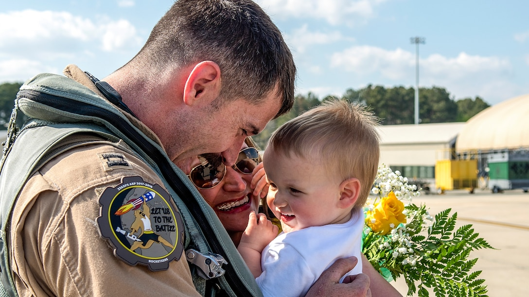 An airman holds a small child.