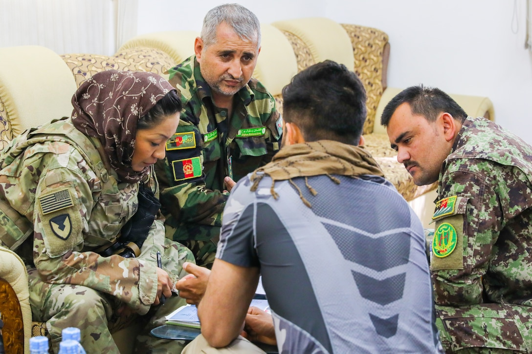 Army Master Sgt. Janet Bretado, logistics advisor for Train, Advise and Assist Command South's military advisory team, meets with her Afghan counterparts in Kandahar, Afghanistan.