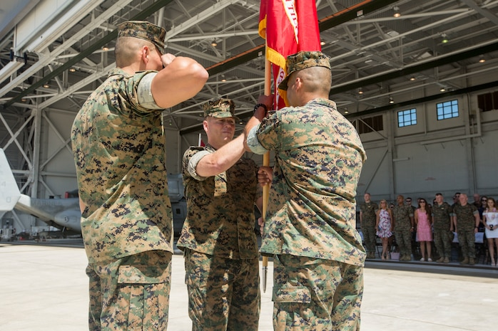 U.S. Marine Corps Lt. Col. Patrick Robinson, off-going commanding officer, Marine Medium Tiltrotor Squadron 268 (VMM-268), passes the Marine Corps flag to Lt. Col. Richard Alvarez during a change of command ceremony, Marine Corps Air Station Kaneohe Bay, Marine Corps Base Hawaii, April 5, 2018. Lt. Col. Robinson retired and relinquished command of the squadron to Lt. Col. Alvarez. (U.S. Marine Corps photo by Lance Cpl. Isabelo Tabanguil)