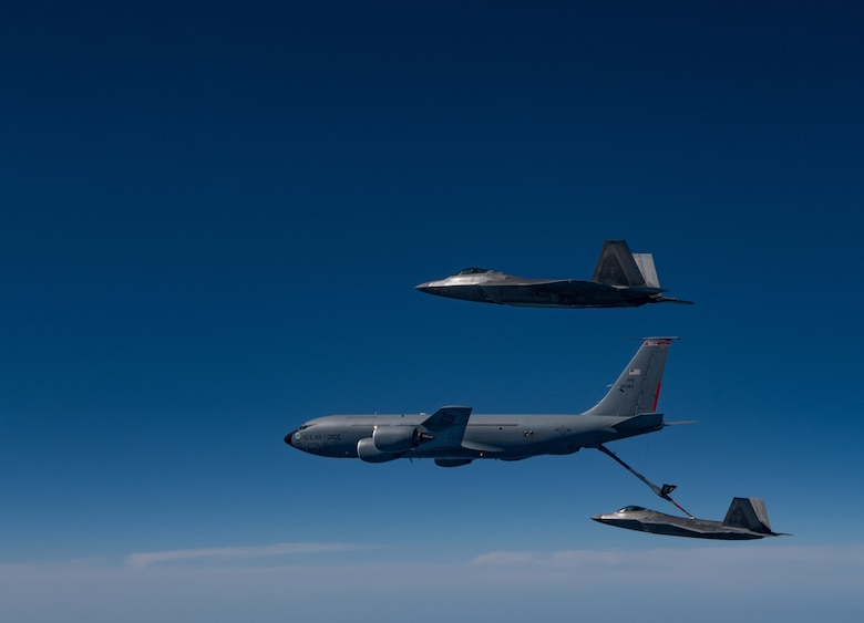 A KC-135 Stratotanker from the 121st Air Refueling Wing refuels F-22 Raptors from the 94th Fighter Squadron and 27th Fighter Squadron over the Atlantic Ocean, April 12, 2018. The 94th FS and 27th FS are the fighter squadrons of the 1st Fighter Wing at Joint Base Langley-Eustis, Va. and the 121st ARW is from Rickenbacker Air National Guard Base, Ohio. (U.S. Air Force photo by Staff Sgt. Carlin Leslie)