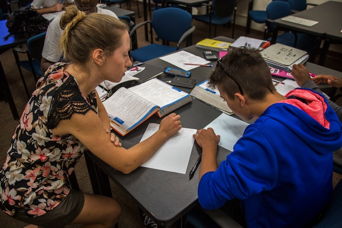 "Lauren Brown, an advanced algebra one teacher from Kailua Intermediate School (KIS), assists a student from KIS with homework during a ""Counting on Math"" tutoring session at the Education Center, Marine Corps Base Hawaii, April 12, 2018. The Count on Math tutoring program focuses on helping students with their mathematics skills while also exploring other subjects. (U.S. Marine Corps photo by Lance Cpl. Matthew Kirk)"