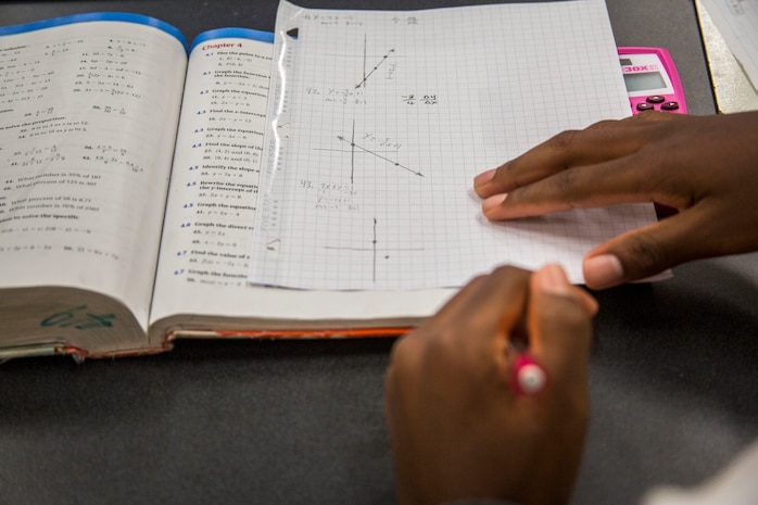 """A student from Kailua Intermediate School works on homework during a """"Counting on Math"""" tutoring session at the Education Center, Marine Corps Base Hawaii, April 12, 2018. The Count on Math tutoring program focuses on helping students with their mathematics skills while also exploring other subjects. (U.S. Marine Corps photo by Lance Cpl. Matthew Kirk)"""
