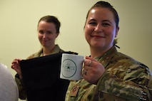 U.S. Air Force Airman 1st Class Crystal Kessler, U.S. Air Forces Central Command (AFCENT) admin, left, and Staff. Sgt. Anastasia Rash, AFCENT communications systems planner, hold promotional items they received during a Sexual Assault Prevention and Response (SAPR) office open house at Shaw Air Force Base, S.C., April 12, 2018.