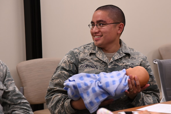 U.S. Air Force Staff Sgt. Mikel Dualos, 20th Medical Operations Squadron medical technician, holds a baby doll during a Dad's 101 class at Shaw Air Force Base, S.C., April 13, 2018.