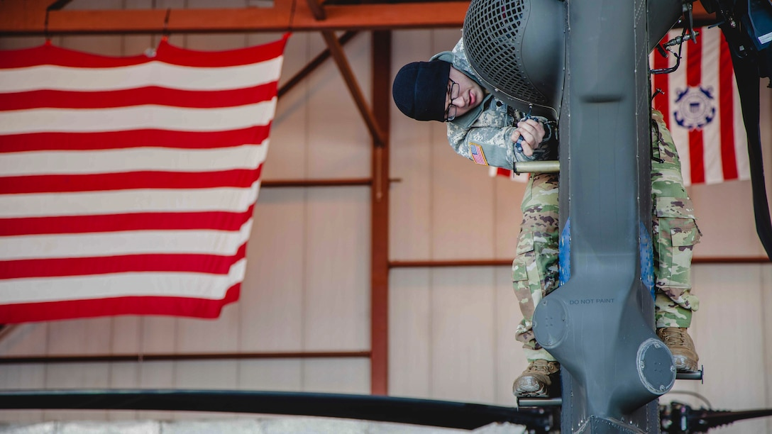 An airman holds onto the tail of a helicopter.
