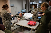 "At center, Master Sgt. Thomas Dissette, 932nd Airlift Wing, 932nd Medical Group, 932nd Aeromedical Staging Squadron, teaches a class on taking care of critically ill patients recently at Scott Air Force Base, Ill.  He works through the steps required to use a piece of equipment called the ""Propaq"", which helps monitor his simulated robotic patient, also known as ""simulation man"" (in background).  The Propaq MD offers multiple display modes to operate in bright sunlight or during night missions (NVG-friendly display). The battery system and AC power charger provide worldwide sea, land, and air operating capabilities for the rugged device.  (U.S. Air Force photo by Lt. Col. Stan Paregien)"