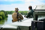A Texas National Guardsman and a Customs and a Border Protection agent discuss the border security mission on the shores of the Rio Grande River.