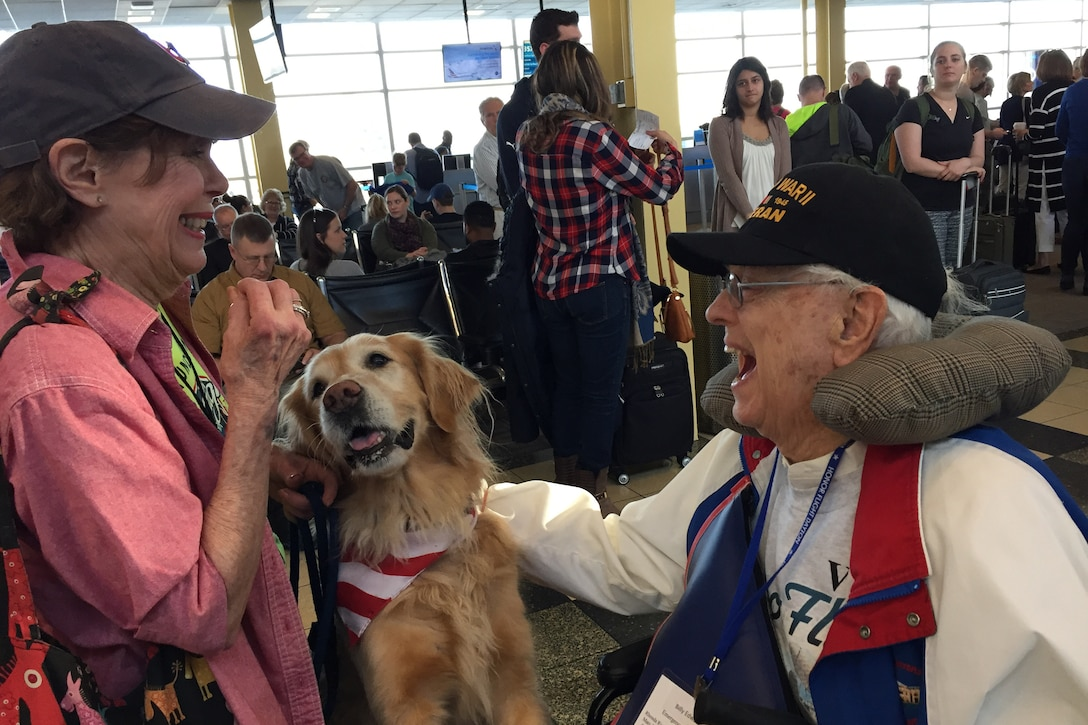 A woman and her dog greet a World War II veteran as he arrives at an airport.