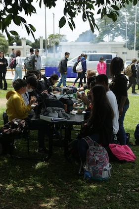 CAMP FOSTER, OKINAWA, Japan – Students sit outside eating during the Kubasaki High School Month of the Military Child barbecue April 10 aboard Camp Foster, Okinawa, Japan.