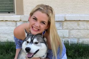 A teen girl poses with her dog.