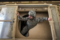 Senior Airman Andrea Rojas-Jimenez, 23d Communications Squadron knowledge manager, climbs out of the top door of a mine-resistant, ambush-protected (MRAP) vehicle roll-over simulator during an Emerge Moody tour, April 12, 2018, at Moody Air Force Base, Ga. Emerge Moody is a program in which select Airmen and civilians tour various units to gain a better understanding of the installations overall mission, capabilities and comprehensive duties. During their tour of the 820th Base Defense Group, Emerge Moody members observed and participated in various demonstrations such as a MRAP rollover simulator, full-mission brief, a sniper display and a tactical gear and static vehicle presentation. (U.S. Air Force photo by Airman 1st Class Eugene Oliver)