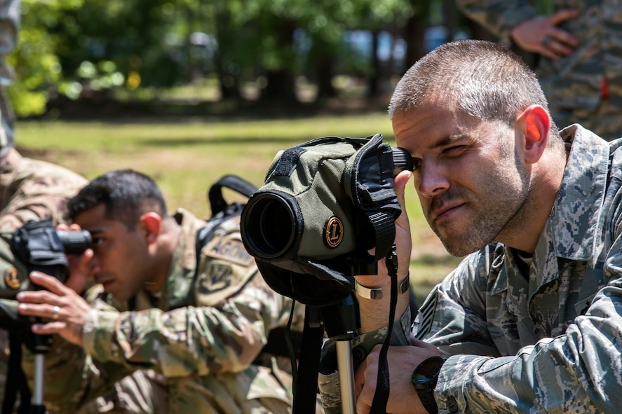 Airmen from Emerge Moody look through a magnified sight, April 12, 2018, at Moody Air Force Base, Ga. Emerge Moody is a program in which select Airmen and civilians tour various units to gain a better understanding of the installations overall mission, capabilities and comprehensive duties. During their tour of the 820th Base Defense Group, Emerge Moody members observed and participated in various demonstrations such as a mine-resistant, ambush-protected vehicle rollover simulator, full-mission brief, a sniper display and a tactical gear and static vehicle presentation. (U.S. Air Force photo by Airman 1st Class Eugene Oliver)