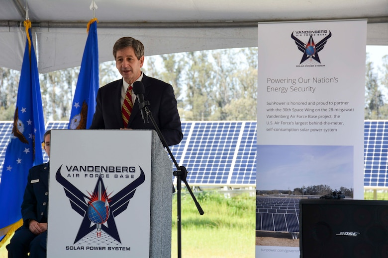 man speaks at podium on stage with rows of solar panels in background
