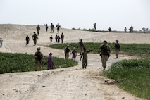 Afghan children follow Marine advisors with Task Force Southwest (TFSW) during a patrol to 6th Sub District Headquarters in Bost Kalay, Afghanistan, March 17, 2018. The movement allowed Marine advisors with TFSW to build rapport with their counterparts in the Afghan National Defense and Security Forces to enhance the unit's train, advise and assist mission in Helmand Province. (U.S. Marine Corps photo by Sgt. Sean J. Berry)