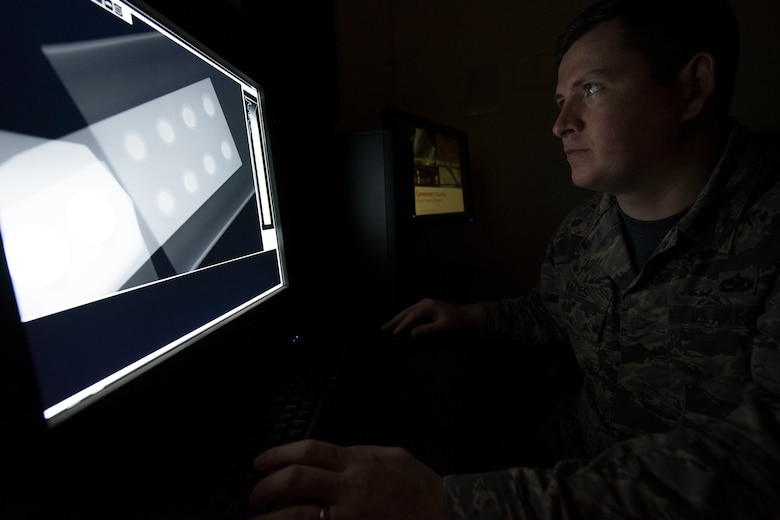 A man looks at a computer screen with an x-ray on it.
