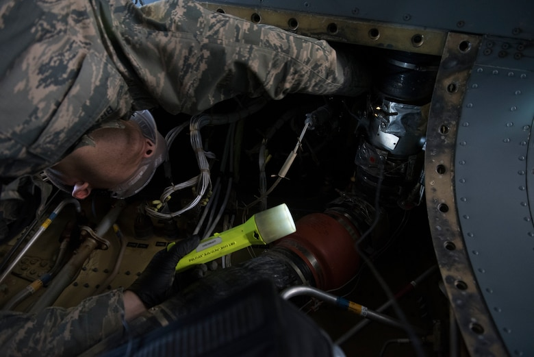 An Airmen uses a flashlight to look at an aircraft part.
