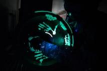 Man puts glowing liquid penetrant on aircraft wheel.