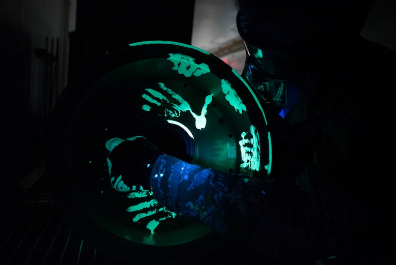 Man puts glowing liquid penetrant on aircraft wheel.
