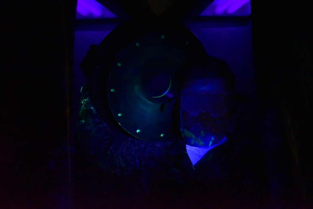 A man holds up an aircraft wheel, with black light surrounding him.