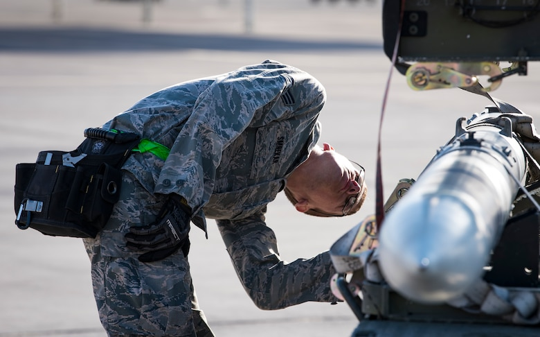 Senior Airman Travis Smrekar, 57th Aircraft Maintenance Squadron weapons loader, prepares a missile to be loaded during a load crew competition at Nellis Air Force Base, Nevada, April 13, 2018. The crews inspected, loaded, and secured two Mark 84 bombs and one AIM-120 AMRAAM onto their respective aircraft.(U.S. Air Force photo by Airman 1st Class Andrew D. Sarver)