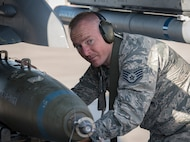 Staff Sgt. Shawn White, 57th Aircraft Maintenance Squadron weapons loader, loads a bomb onto an F-16 Fighting Falcon fighter jet during a load crew competition at Nellis Air Force Base, Nevada, April 13, 2018. The competition challenges the teams' ability to load munitions on aircraft in an accurate, safe and timely manner.(U.S. Air Force photo by Airman 1st Class Andrew D. Sarver)