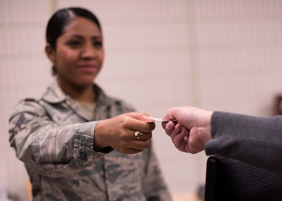 Airman 1st Ruby Bennett, 92nd Force Support Squadron Military Personnel Flight force management technician, hands a military dependent a new identification card at Fairchild Air Force Base, Washington, April 5, 2018. The 92nd MPF has deployed a new online dependent ID card registration website that allows military sponsors to submit paperwork ahead of physically picking up a new ID card, saving considerable time. (U.S. Air Force photo/Senior Airman Ryan Lackey)