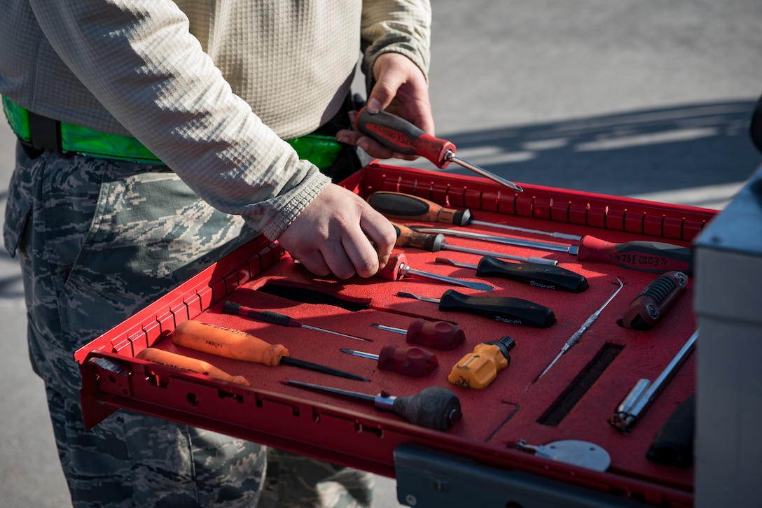 Senior Airman Austin Reynolds, 57th Aircraft Maintenance Squadron weapons loader, picks up a screwdriver during a load crew competition at Nellis Air Force Base, Nevada, April 13, 2018. The crews inspected, loaded, and secured two Mark 84 bombs and one AIM-120 AMRAAM onto their respective aircraft.(U.S. Air Force photo by Airman 1st Class Andrew D. Sarver)