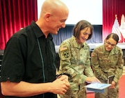 Col. Deydre Teyhen (center), guest speaker for the Ready and Resilient campaign, shows a Soldier and a Department of Defense civilian the Army's Performance Triad application on a tablet device at the main theater at Joint Base San Antonio-Fort Sam Houston April 13.