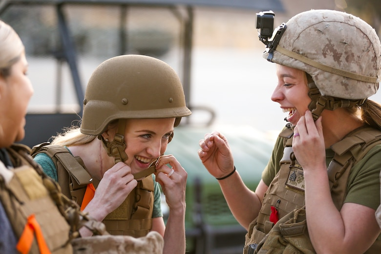 Brandi Pompa, wife of Sgt. Isaac Pompa, scouts, Alpha Company, 1st Tank Battlion, and Katherine Shelton, wife of Cpl. Chad Shelton, scouts, Alpha Company, 1st Tanks, adjust their kevlar helmets during the unit's Jane Wayne Spouse Appreciation Day aboard the Marine Corps Air Ground Combat Center, Twentynine Palms, Calif., April 3, 2018. The purpose of the event is to build resiliency in spiritual well being, the will to fight and a strong home life for the 1st Tanks Marines and their families. (U.S. Marine Corps photo by Lance Cpl. Rachel K. Porter)