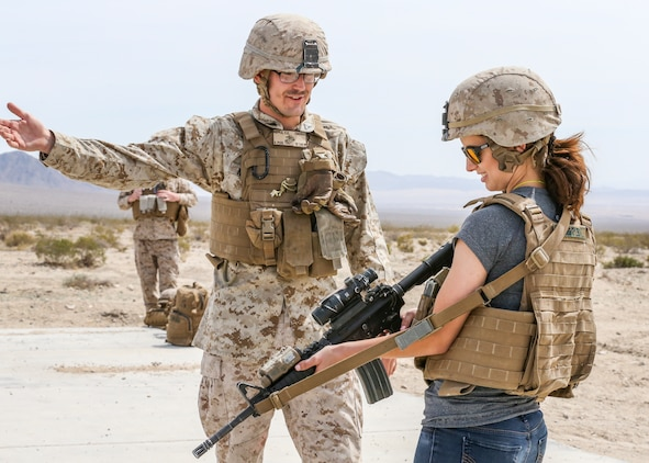 Sara Nepple, wife of Cpl. Caleb Nepple, gunner, Alpha Company, 1st Tank Battalion, receives instruction on how to fire the M16A4 service rifle from her husband during the unit's Jane Wayne Spouse Appreciation Day aboard the Marine Corps Air Ground Combat Center, Twentynine Palms, Calif., April 3, 2018. The purpose of the event is to build resiliency in spiritual well being, the will to fight and a strong home life for the 1st Tanks Marines and their families. (U.S. Marine Corps photo by Lance Cpl. Rachel K. Porter)