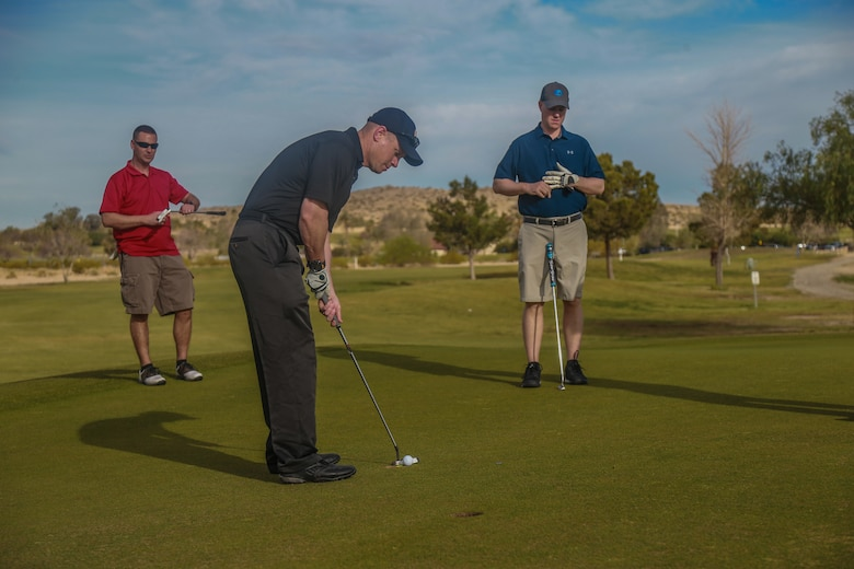 Lt. Col. Roy Miner, advanced individual training officer-in-charge, Marine Corps Logistics Operations Group, putts in on the 9th hole at the first-ever True Grit Tournament at the Desert Winds Golf Course aboard the Marine Corps Air Ground Combat Center, Twentynine Palms, Calif., April 6, 2018. The tournament was held to raise money for MCLOG's Marine Corps Birthday Ball while also building relations between the host unit and other units on base. (U.S. Marine Corps photo by Lance Cpl. Preston L. Morris)