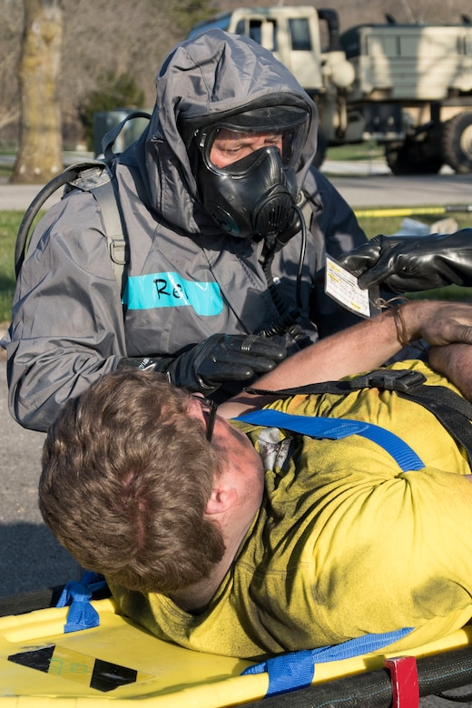 South Carolina National Guard Sgt. Paul Reid and other medics from the 251st Area Support Medical Company, in-process simulated casualties, April 12, 2018, during a drill at Muscatatuck Urban Training Center, Indiana, as part of Exercise Vibrant Response.