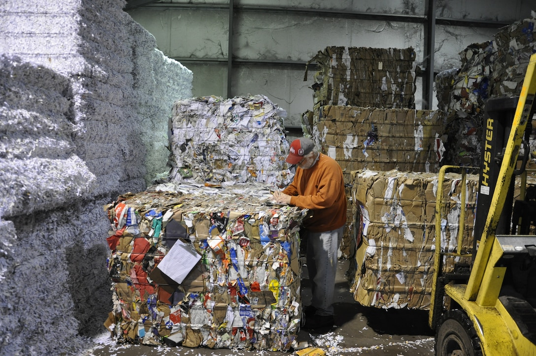 Roger Smart records the tonnage for recycled bales of paper stacked high inside the Base Recycling Center (U.S. Air Force photo/W. Eugene Barnett, Jr.)