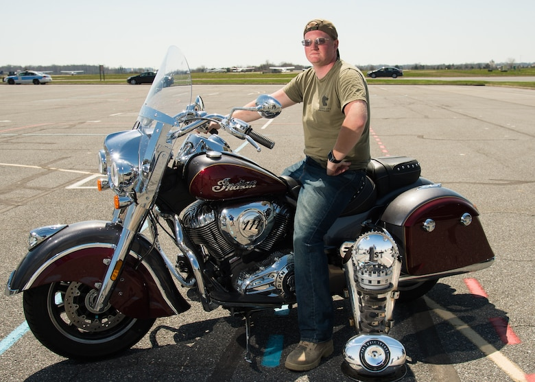 Senior Airman Ronald Naugle, 436th Aerial Port Squadron special handling processor, shows off his motorcycle and trophy during Motorcycle Safety Day April 13, 2018, at Dover Air Force Base, Del. Naugle's 2017 Indian was selected from about 120 motorcycles as the best overall bike. (U.S. Air Force photo by Mauricio Campino)