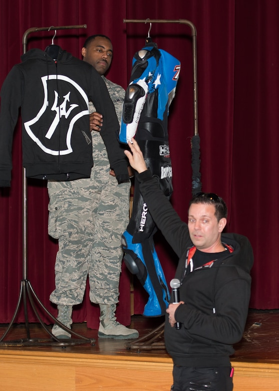 Staff Sgt. Kenneth Reid, 436th Airlift Wing occupational safety technician and wing motorcycle safety representative, holds a motorcycle jacket while Todd McNabney, owner and creative designer of Heroic Racing Apparel, speaks at the Annual Pre-Season Brief during Motorcycle Safety Day April 13, 2018, at Dover Air Force Base, Del. McNabney was one of four speakers who kicked off the annual event. (U.S. Air Force photo by Mauricio Campino)