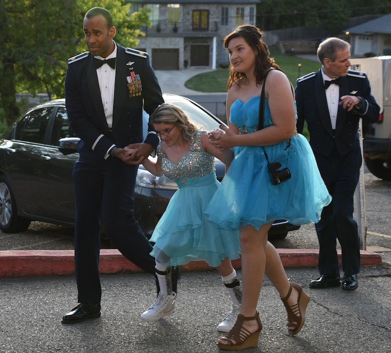 U.S. Air Force Maj. Theo Panton, assigned to the 11th Bomb Squadron at Barksdale Air Force Base, Louisiana, escorts attendees to the El Karubah Shriners' Memories in Wonderland Ball, Shreveport, La., April 14, 2018.