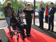 Jayne Smith provides and escort down the red carpet at the El Karubah Shriners' Memories in Wonderland Ball at the Shriners' Clubhouse in Shreveport, Louisiana, April 14, 2018.