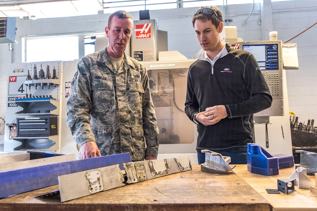 Tech. Sgt. Bradley Duncan, 436th Maintenance Squadron metals technology section chief explains to Joey Logano, driver of the No. 22 Ford in the Monster Energy NASCAR Cup Series, how the metals technology section fabricates aircraft parts April 11, 2018, at Dover Air Force Base, Del. Duncan told Logano that a plastic version of an aircraft part is made first by using Computer Numerical Controlled (CNC) machining capabilities prior to fabricating a final version from stock metal. (U.S. Air Force photo by Roland Balik)
