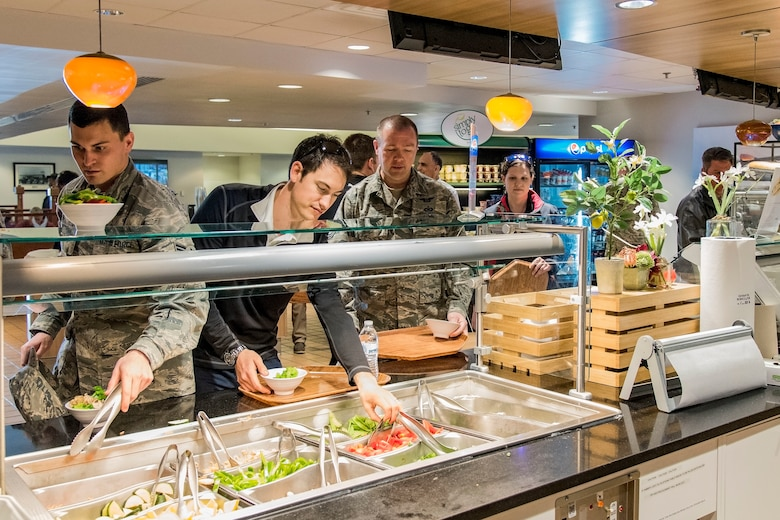 Joey Logano, driver of the No. 22 Ford in the Monster Energy NASCAR Cup Series, followed by Tech. Sgt. Jerry Ivey, 436th Airlift Wing Command Post senior emergency action controller, go through the food line at the Patterson Dining Facility April 11, 2018, on Dover Air Force Base, Del. Logano had lunch with Team Dover members during his five-hour tour of the base. (U.S. Air Force photo by Roland Balik)