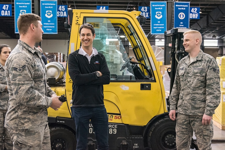 "Airman 1st Class Austin Harris (left) and Senior Airman William Phillips, 436th Aerial Port Squadron cargo processors, speak with Joey Logano, driver of the No. 22 Ford in the Monster Energy NASCAR Cup Series, during his visit to the Super Port April 11, 2018, at Dover Air Force Base, Del. Logano is scheduled to compete in the ""AAA 400 Drive for Autism"" Monster Cup Series race on Sunday, May 6 at Dover International Speedway. (U.S. Air Force photo by Roland Balik)"