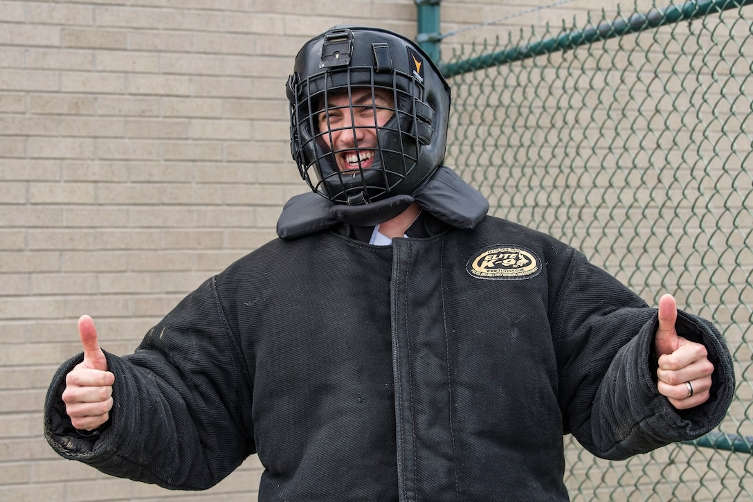 """Joey Logano, driver of the No. 22 Ford in the Monster Energy NASCAR Cup Series, gives the """"thumbs up"""" sign as he prepares to enter the 436th Security Forces Squadron military working dog training area April 11, 2018, at Dover Air Force Base, Del. Logano donned the protective bite suit in preparation for a demonstration involving him and Karlo, an 80-pound Belgian Malinois. (U.S. Air Force photo by Roland Balik)"""