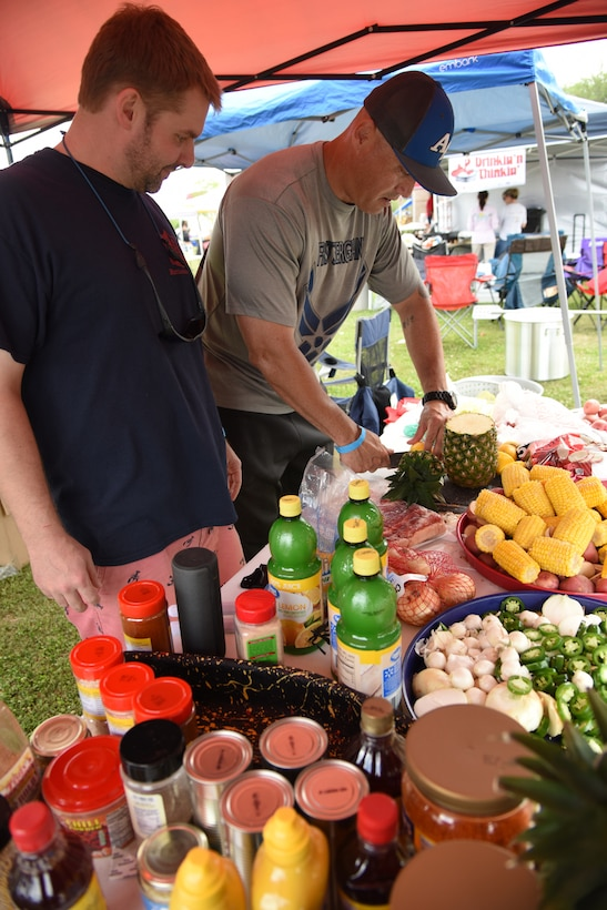 """First Sergeants Council"" team members, Dustin Polovich and U.S. Air Force Master Sgt. Billy Dunn, 335th Training Squadron first sergeant, prepare the 'fixins' during the 6th Annual Bay Breeze Crawfish Cook-Off at the Bay Breeze Event Center at Keesler Air Force Base, Mississippi, April 13, 2018. The ""Craw-Fish Pot-Nahs"" won first place overall and a free entry into the 26th Annual Mississippi Coast Coliseum Crawfish Festival Cook-Off. Over 800 Keesler personnel attended the event and almost 1700 pounds of crawfish was distributed. (U.S. Air Force photo by Kemberly Groue)"