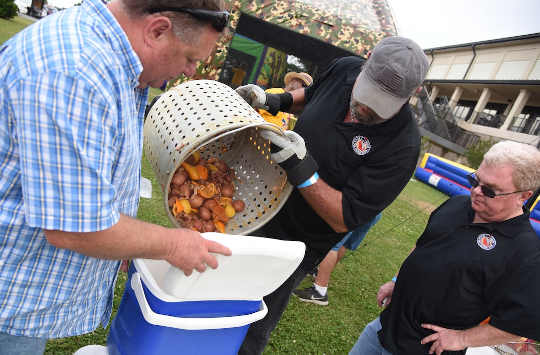 """Crawfish Daddies"" team members, Rob Erman, 2nd Air Force program manager, Ronald McCarty and Brett Long, 81st Infrastructure Division housing chief, dump the 'fixins' from their crawfish boil into a cooler during the 6th Annual Bay Breeze Crawfish Cook-Off at the Bay Breeze Event Center at Keesler Air Force Base, Mississippi, April 13, 2018. The ""Craw-Fish Pot-Nahs"" won first place overall and a free entry into the 26th Annual Mississippi Coast Coliseum Crawfish Festival Cook-Off. Over 800 Keesler personnel attended the event and almost 1700 pounds of crawfish was distributed. (U.S. Air Force photo by Kemberly Groue)"