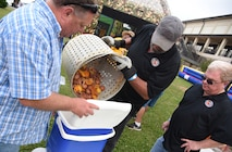 """""""Crawfish Daddies"""" team members, Rob Erman, 2nd Air Force program manager, Ronald McCarty and Brett Long, 81st Infrastructure Division housing chief, dump the 'fixins' from their crawfish boil into a cooler during the 6th Annual Bay Breeze Crawfish Cook-Off at the Bay Breeze Event Center at Keesler Air Force Base, Mississippi, April 7, 2017. The """"Craw-Fish Pot-Nahs"""" won first place overall and a free entry into the 26th Annual Mississippi Coast Coliseum Crawfish Festival Cook-Off. Over 800 Keesler personnel attended the event and almost 1700 pounds of crawfish was distributed. (U.S. Air Force photo by Kemberly Groue)"""